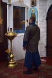 Ridder in de middeleeuwse kleding van de kettingspost en het bidden in kerk vóór een pictogram Royalty-vrije Stock Foto's