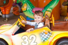On the ride. Beautiful boy having fun on the ride at the local carnival Royalty Free Stock Photography