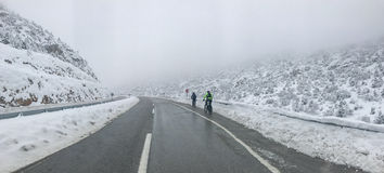 Ride a bike in snowy weather. Biker and road ; ride a bike in snowy weather stock photography