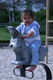 Ride the Bunny. Young girl playing on playground royalty free stock photography
