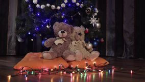 Ride a camera on two toy teddy bears sitting on orange pillows near a Christmas decoration tree. Christmas decor. Apartment, soft toys, luminous garlands 4k stock video footage