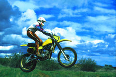 Ride in the clouds. Motto x rider jumping his motorcycle  on a neat  day with clouds and blue shys Royalty Free Stock Photography
