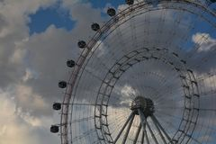 Ride the clouds. Huge ferriswheel against the backdrop of billowy clouds on a clear beautiful day Royalty Free Stock Image