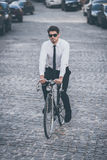 Ride it. Full length rear view of handsome well-dressed young man in sunglasses riding his bicycle outdoors Royalty Free Stock Photography