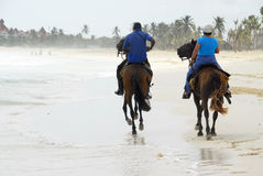 Ride on horseback on the beach. Two people were on horseback by the beautiful Macao beach in Punta Cana, Dominican Republic royalty free stock photos