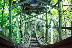 Ride Through the Jungle nature taking over Old fun. Here is an image of a abandoned amusement park where this Roller Coaster sits abandoned Stock Photos