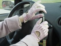 Ride me pink. Women ride a car with drive leather pink gloves Royalty Free Stock Photos