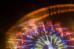 Ride in motion at the amusement park, night illumination. Long exposure.  stock photos