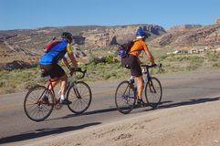 Ride the Rockies. Two cyclists with the Colorado National Monument in the background Royalty Free Stock Photography