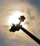Ride in Silhouette. An amusement park ride silhouettes against the sun as it swoops into the sky Royalty Free Stock Photos