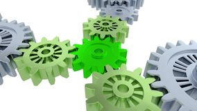 Ride Under and Above Silver Gears Focused on One Small Green Gear. With a white background stock illustration