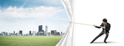 Rideau blanc s'ouvrant en jeune homme et présentation du paysage moderne de ville photos stock