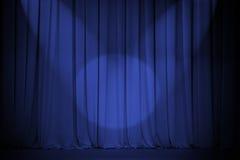 Rideau bleu en théâtre avec la croix de deux lumières Photos stock