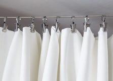 Rideau crème accrochant sur une ficelle sur des crochets en métal illuminés par lumière du jour Photographie stock