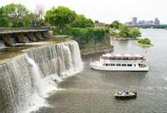Rideau Falls Ottawa, Ontario, CAnada. A view of a tour boat, fishing boat at the base of the Rideau Falls in Ottawa, ontario, Canada Stock Photo