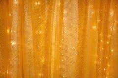 Rideau jaune avec des lumières dans le dos Photos stock
