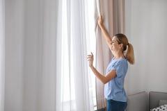 Rideaux en ouverture de femme et regard hors de la fenêtre à la maison photographie stock libre de droits