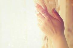 Rideaux en ouverture de la main de la femme dans une chambre à coucher image filtrée par éclat de lumière naturelle avec le foyer Photos stock