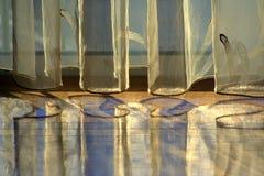 Rideaux en soie réfléchis sur l'étage en bois.   Image libre de droits