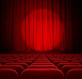 Rideaux rouges en théâtre ou en cinéma avec le projecteur et les sièges Photos libres de droits