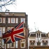Riden ut brittisk flagga mot traditionella byggnader Royaltyfri Fotografi