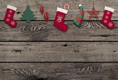riden ut gammal träbakgrund med gulliga hängande julbeståndsdelar Royaltyfria Bilder