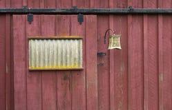 Riden ut röd ladugårddörr med det ljusa fasta tillbehöret Royaltyfri Foto