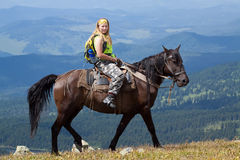Rider with backpack on horseback Stock Image