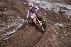 Rider at the beginning of rut turning. The driver put the right foot forward at the beginning of a deep rut turning sandy motocross track Stock Photo