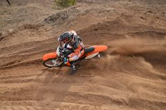 Rider at the beginning of rut turning sandy MX  track Royalty Free Stock Image