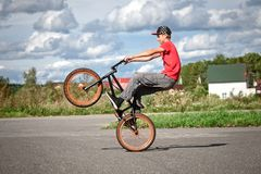A rider on a bicycle does tricks.  royalty free stock photography