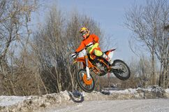 Rider on bike for MX flies over hill on snowy highway Royalty Free Stock Image