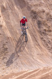 Rider on a bike, with a steep hill Royalty Free Stock Image