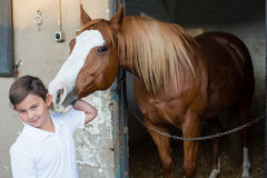 Rider boy caressing a horse. Portrait of rider boy caressing a horse Stock Image
