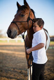 Rider boy caressing a horse in the ranch Royalty Free Stock Photos