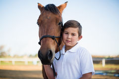 Rider boy caressing a horse in the ranch Stock Images