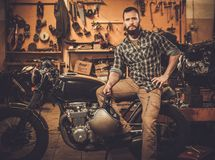 Rider and cafe-racer motorcycle. Rider and his vintage style cafe-racer motorcycle in customs garage stock images