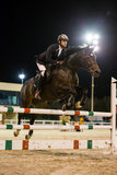 Rider competes in horse jumping competition Royalty Free Stock Images