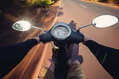 Rider driving scooter on an asphalt road. Motion blurred backgro. Und. First-person view Royalty Free Stock Images
