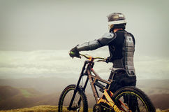 The rider in the full-face helmet and full protective equipment on the mtb bike stands on a rock against the background Stock Photos