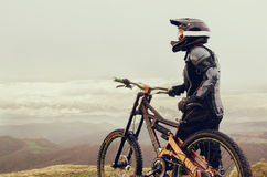 The rider in the full-face helmet and full protective equipment on the mtb bike stands on a rock against the background Royalty Free Stock Images