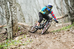 The rider in the full-face helmet passes a counter-rotation in the glide against the background of a misty forest. The young man in the full-face helmet passes Stock Photo