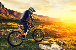 The rider in full protective equipment on the mtb bike is riding toward the sunset in the rays of the sunset sun against royalty free stock images