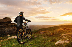 The rider in full protective equipment on the mtb bike is riding toward the sunset in the rays of the sunset sun against Royalty Free Stock Photo