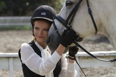 Ukraine, Kiev. The rider girl hugs the horse`s head. The rider girl hugs the horse`s head. Smiling rider, stroking the horse`s head royalty free stock photo