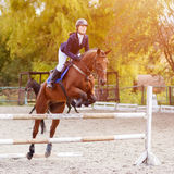 Rider girl jumping over hurdle on show jumping Stock Photos