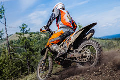 Rider going down a hill, dirt and stones from under wheels Stock Images