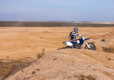 Rider on his bike rides through the hills of the desert Stock Photography