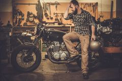 Rider and his vintage style cafe-racer motorcycle. In custom garage royalty free stock images