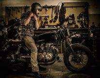 Rider and his vintage style cafe-racer motorcycle. In customs garage royalty free stock images
